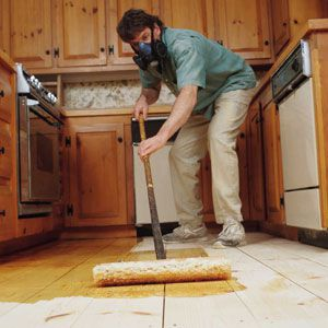 Person applying a wood floor finish made of polyurethane with a lamb wool applicator.