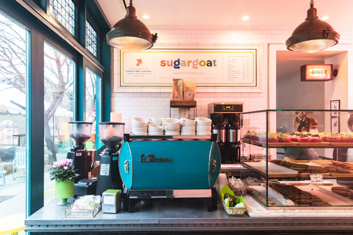 A bakery counter with a bright blue espresso machine beside a glass case of cupcakes and cookies.