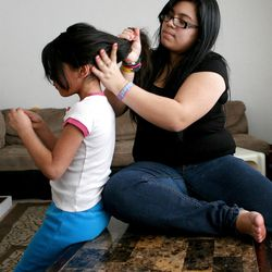 Mariza Carreon, 6, gets her hair done by her sister Tatiana, 15, at home in Taylorsville on Saturday, Feb. 9, 2013. Carreron's family was recently evicted, but they managed to land on their feet.