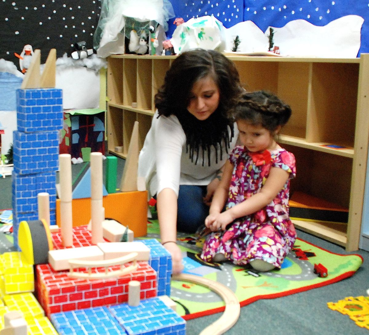 Teacher Rosa Figueroa plays with a child at the Early Excellence Program of Denver.
