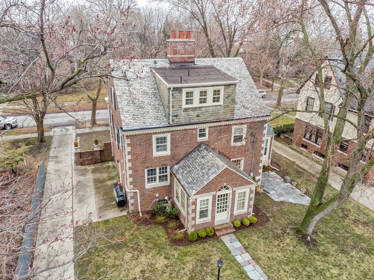 Aerial view of the brick home with its gabled roof and small sunroom attached to the back.