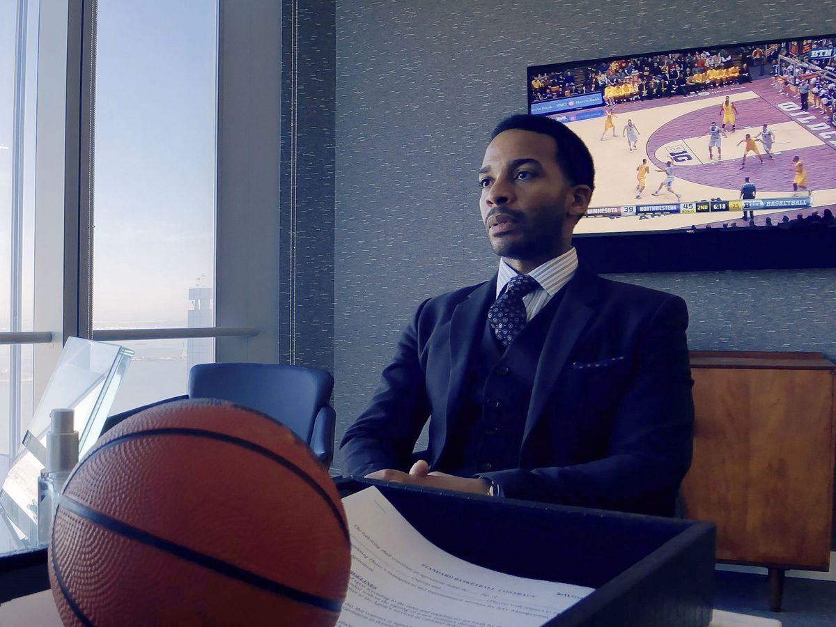 A man in a suit sits at a desk with a basketball in the foreground and a basketball game on a TV in the background.