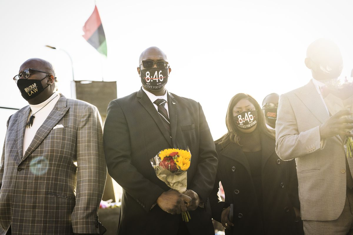 Flanked on either side by Black men in light colored suits, Philonise — wearing sunglasses, a black suit, white shirt, and a tie with brown, blue, and white stripes — holds bouquet of yellow and red flowers. He has on a mask that says 8:46; originally, it was believed George Floyd was restrained by Chauvin for eight minutes and 46 seconds. The trial has clarified that it was actually more like nine minutes and 46 seconds.