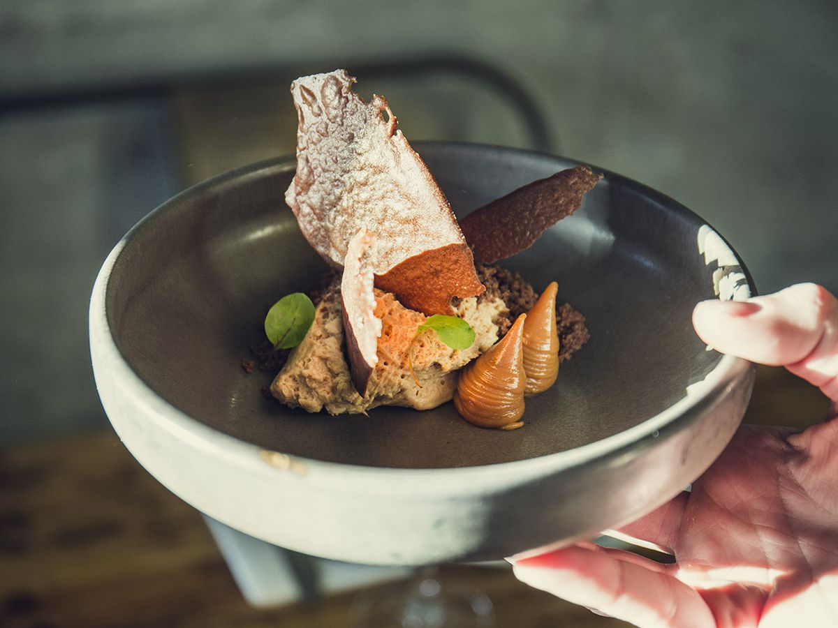A sunlit hand holds a shallow slate bowl of various textured and shaped foods, including small spires, tall chips and thick mousse