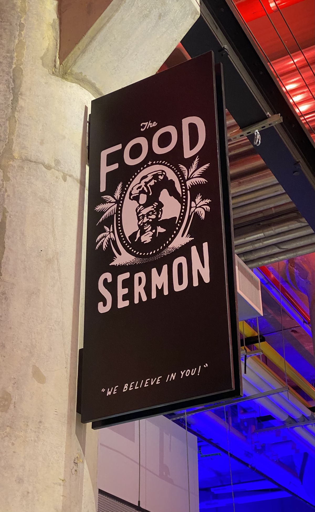 """A pink and black sign for the Food Sermon hands on a concrete pillar, reading, """"We believe in you."""""""