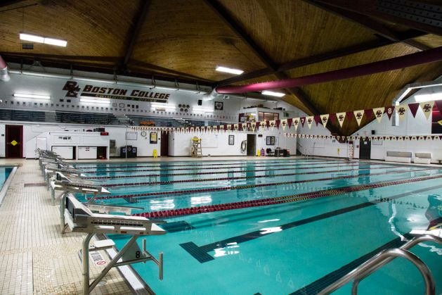 An indoor swimming pool with lanes and diving boards. There is a string of flags hanging over the pool.