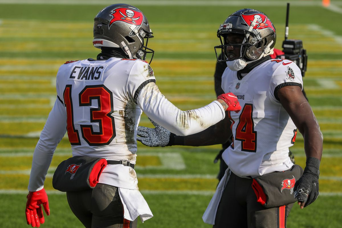 Mike Evans #13 and Chris Godwin #14 of the Tampa Bay Buccaneers celebrate after Evans caught a touchdown pass in the first quarter against the Green Bay Packers during the NFC Championship game at Lambeau Field on January 24, 2021 in Green Bay, Wisconsin.