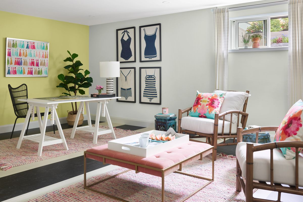 A beach themed home office with two bamboo chairs a large ottoman and a drafting desk.