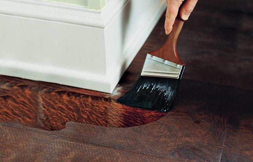 Paint Brush Applying Finish Around Corners Of Hardwood Floor