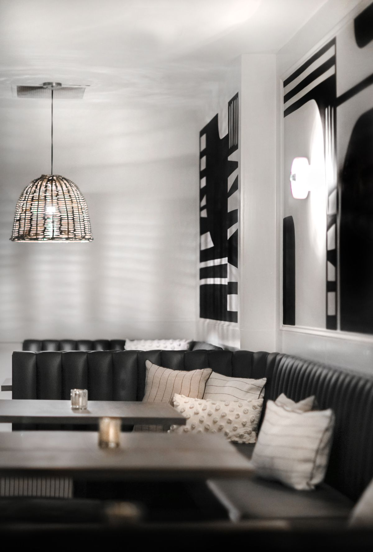 A black leather banquette featuring natural colored throw pillows curves into the corner with two tables in front of it