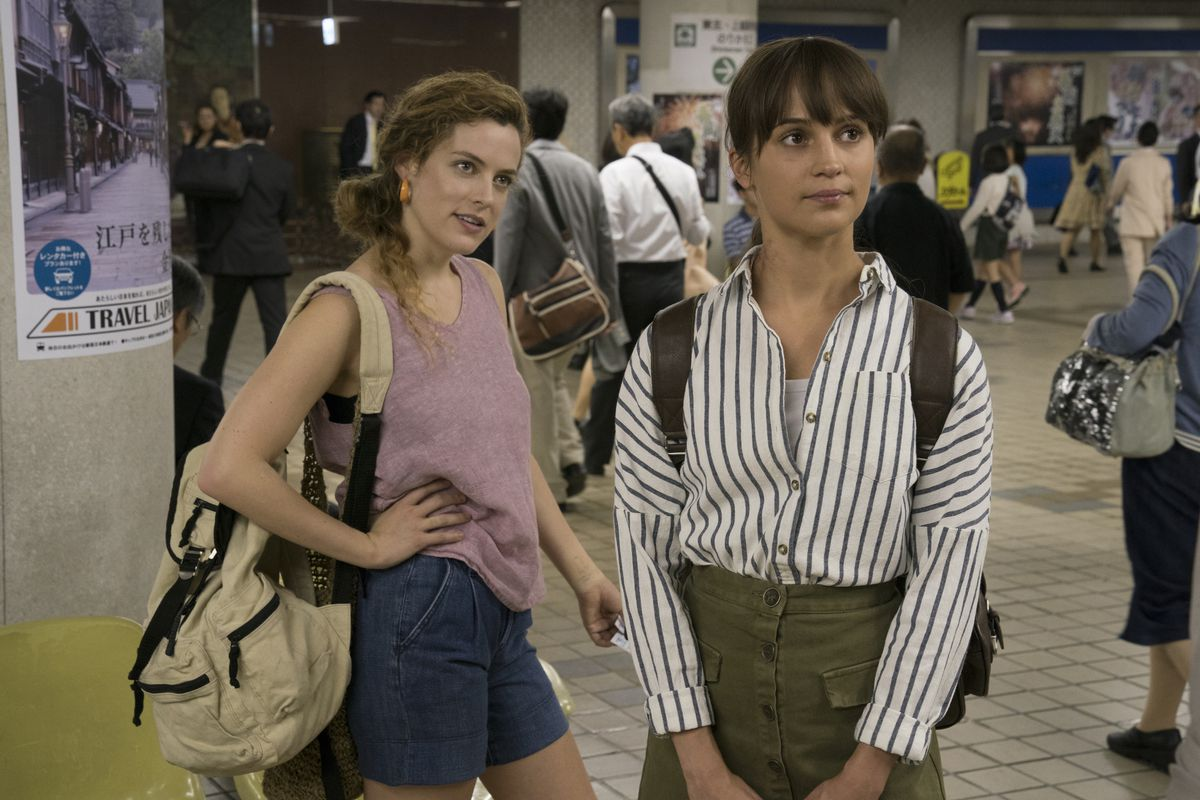 The two women look expectant as they stand in the middle of a train station.