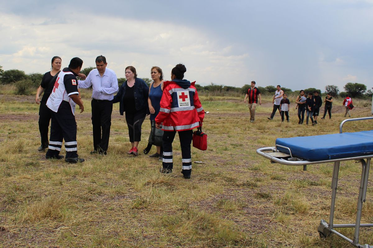 In this photo released by Red Cross Durango communications office, Red Cross workers attend airline passengers who survived a plane crash, as they walk away from the crash site in a field near the airport in Durango, Mexico, Tuesday, July 31, 2018. An Aer