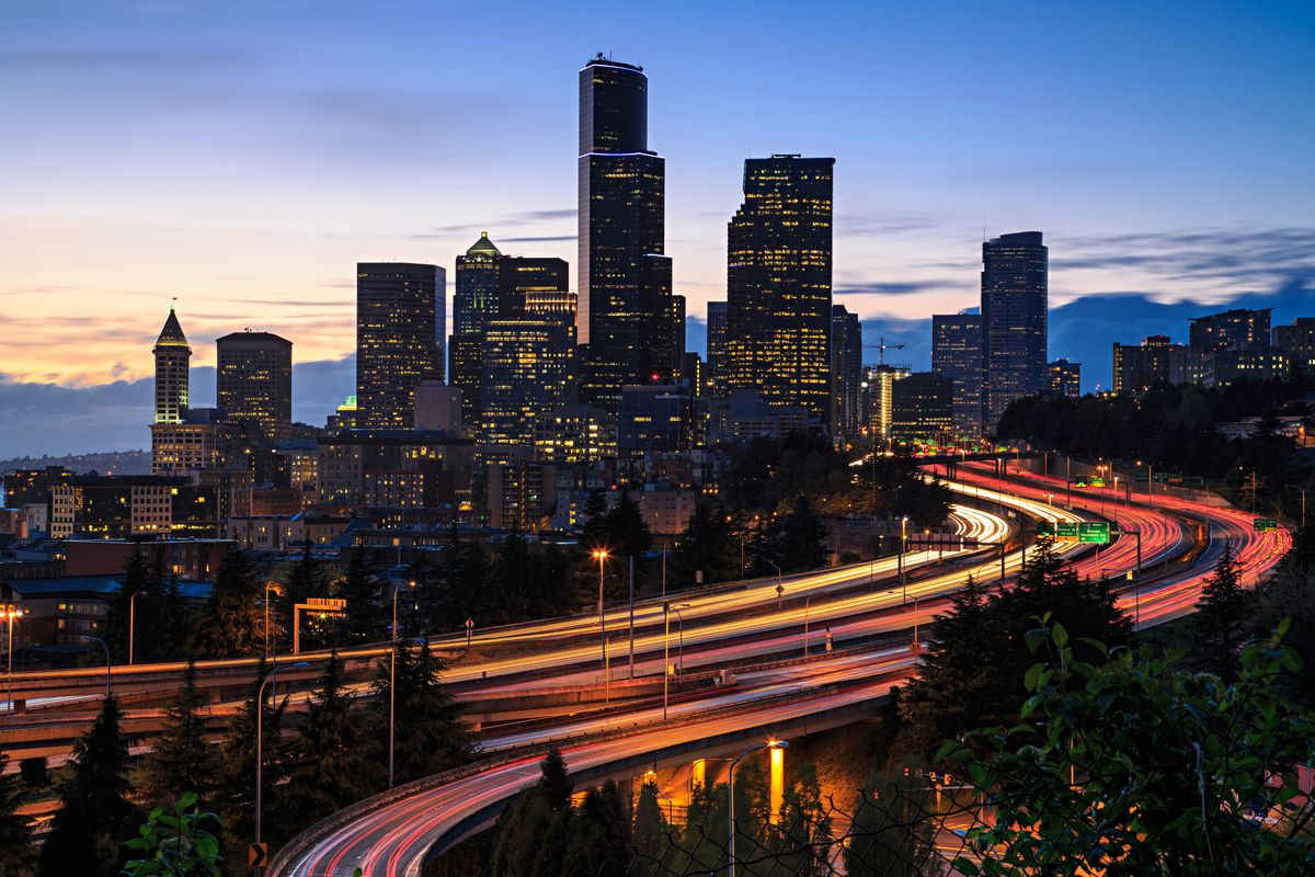 Downtown Seattle skyline at twilight, with streaks of lights on highways indicating cars traveling (time-lapse) and the Smith Tower visible to the left