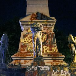 The statues on the Confederate monument are covered in graffiti and beheaded after a protest in Portsmouth, Va., Wednesday, June 10, 2020. Protesters beheaded and then pulled down four statues that were part of a Confederate monument. The crowd was frustrated by the Portsmouth City Council's decision to put off moving the monument.