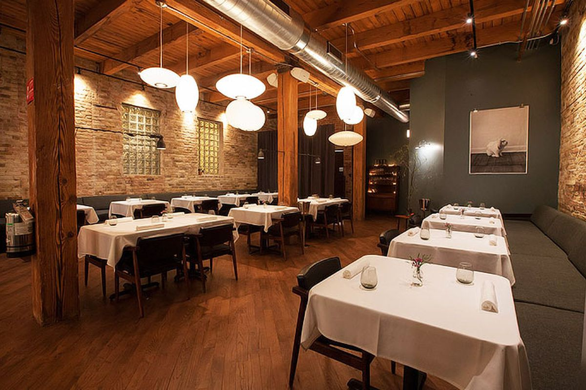 A low-lit dining room with lots of wood and white tablecloths.