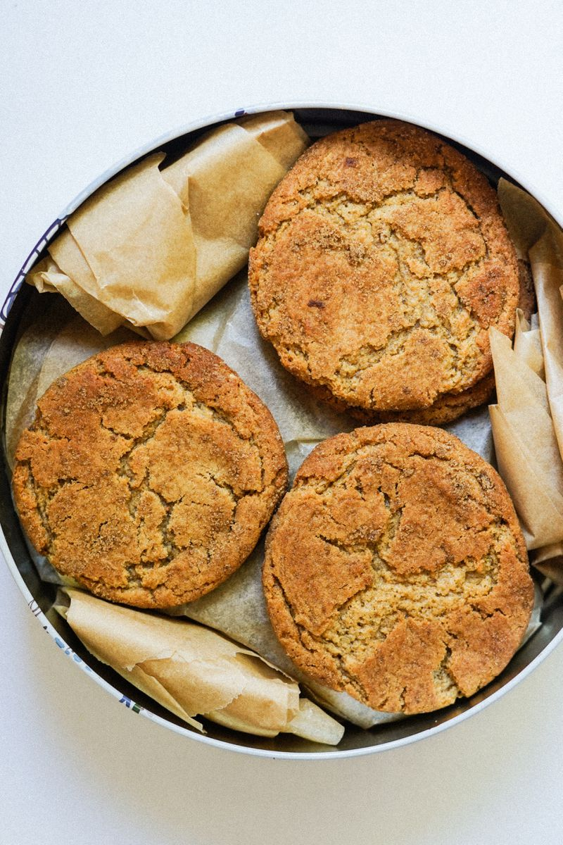 Three stacks of round peanut butter iso cookies, in between layers of parchment paper, in a tin.