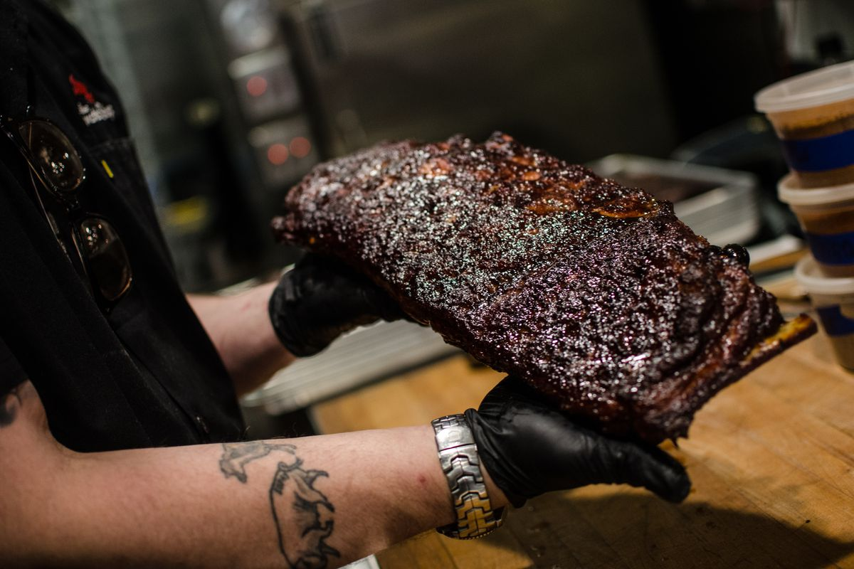 Two hands, wearing black gloves, hold a piece of barbecue meat above a wooden counter