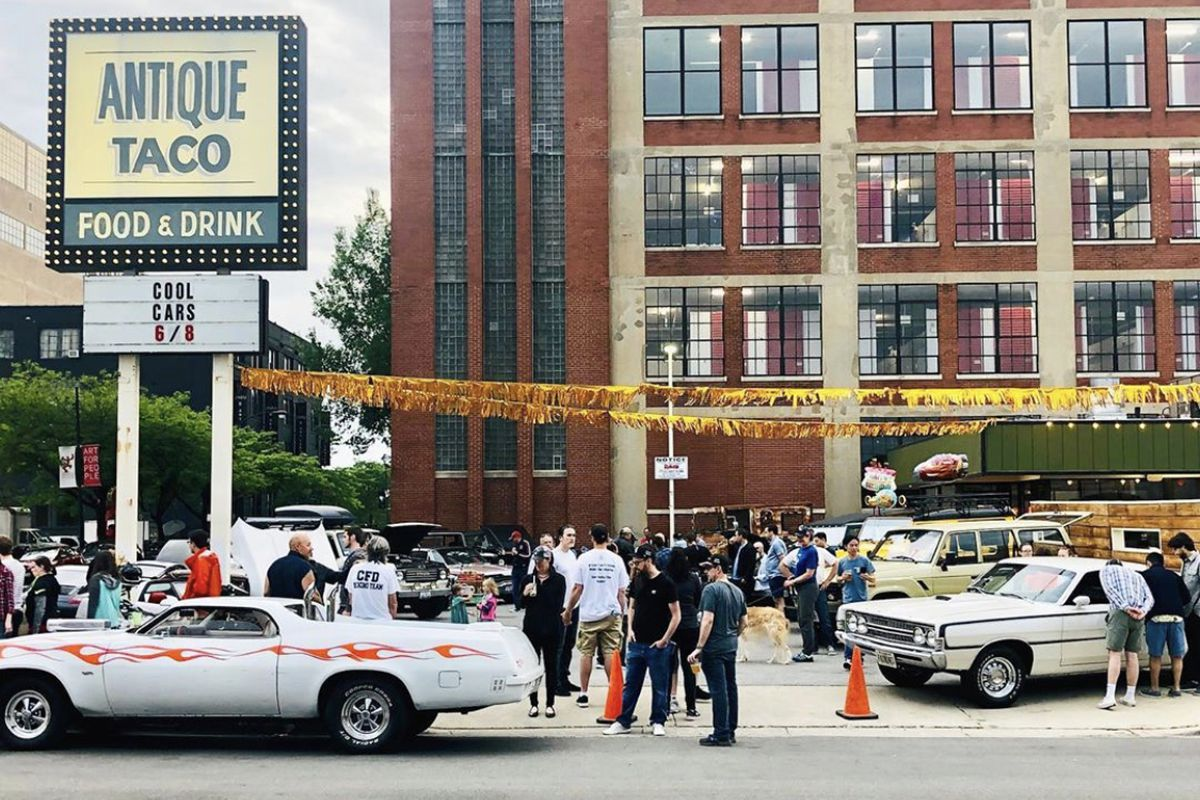 """People standing around outside looking at classic cars beside a large sign that reads """"Antique Taco Food & Drink"""""""