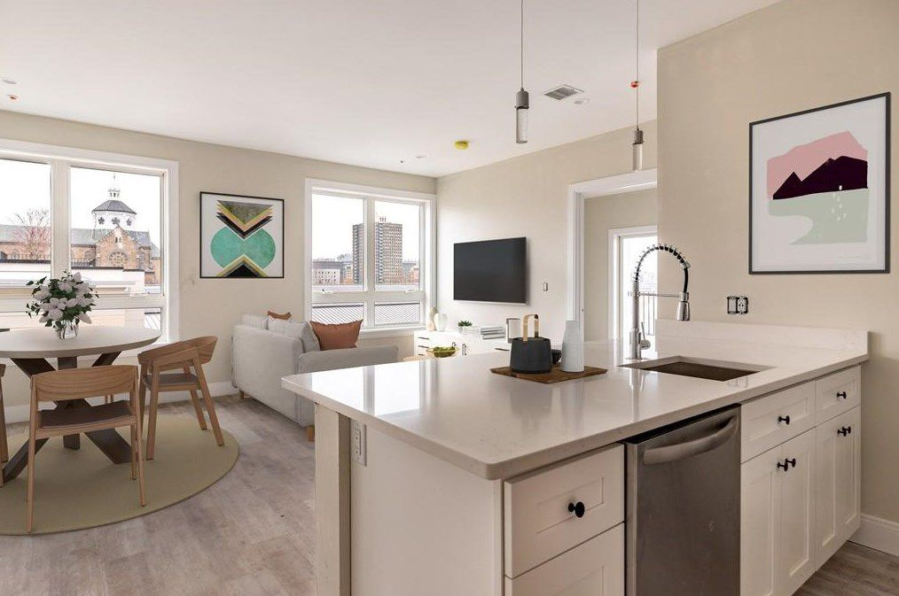 A view of an open living room-dining room over the same kitchen island.