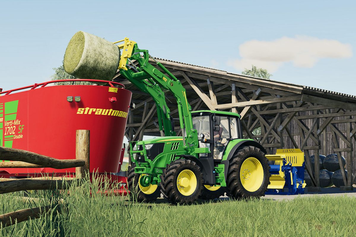 a green John Deere utility vehicle dumps a giant roll of hay from its spindle attachment into a large red bin in Farming Simulator 19