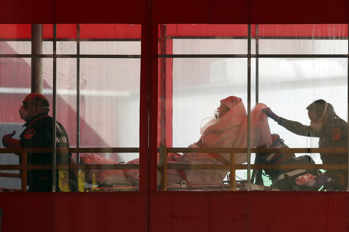Emergency medical technicians wheel a patient into Elmhurst Hospital Center's emergency room, Tuesday, April 7, 2020, in the Queens borough in New York, during the current coronavirus outbreak. (AP Photo/Kathy Willens)