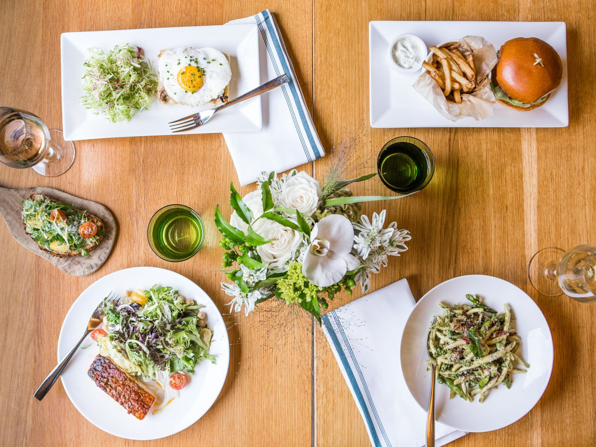 overhead shot of white plates with food on a wood table