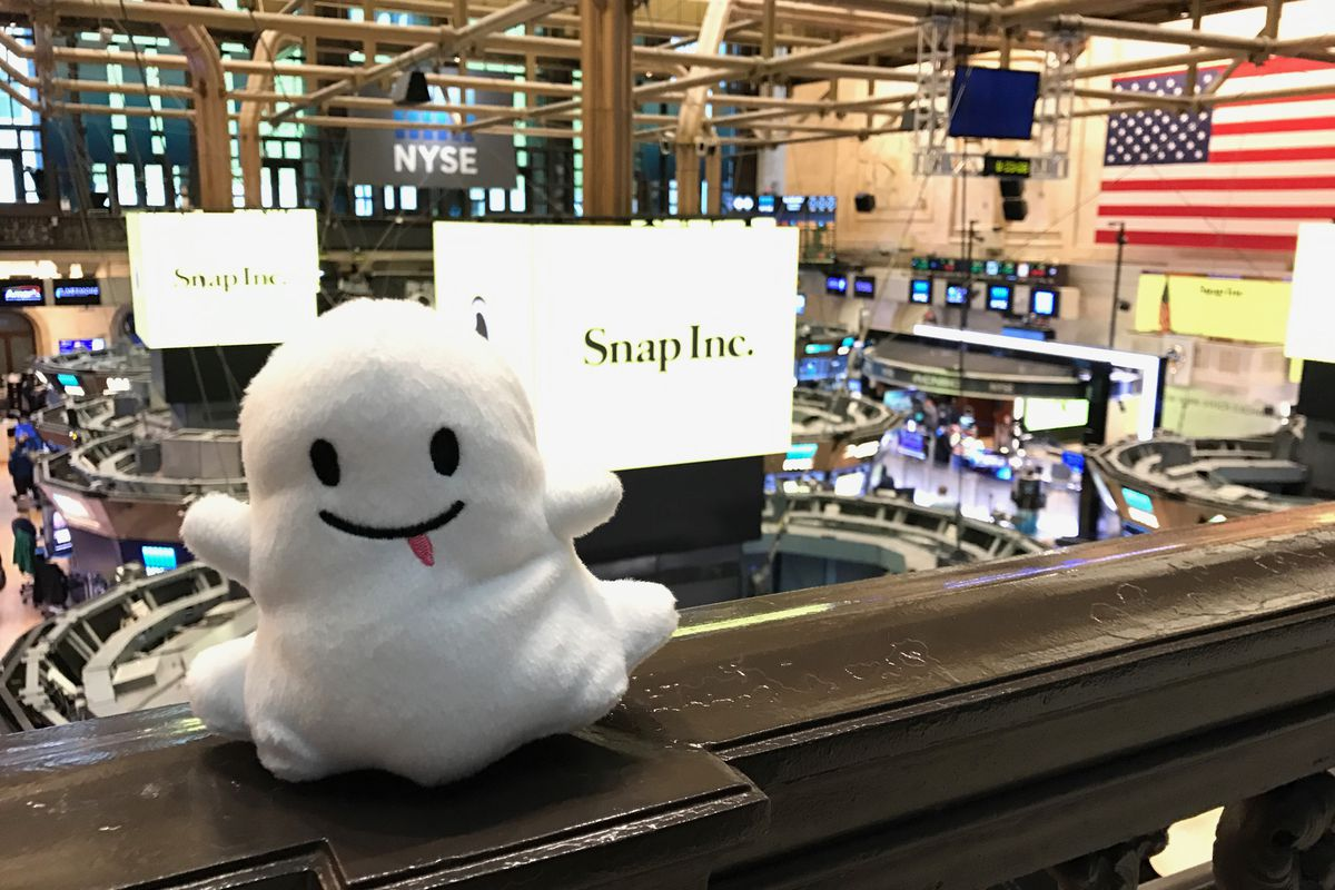 A stuffed and smiling ghost — the symbol for Snapchat — sits on a railing with the New York Stock Exchange in the background.