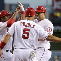 Los Angeles Angels' Kendrys Morales, right, celebrates his three-run home run with Howard Kendrick, left, and Albert Pujols during the first inning against the Oakland Athletics in a baseball game in Anaheim, Calif., Monday, April 16, 2012.