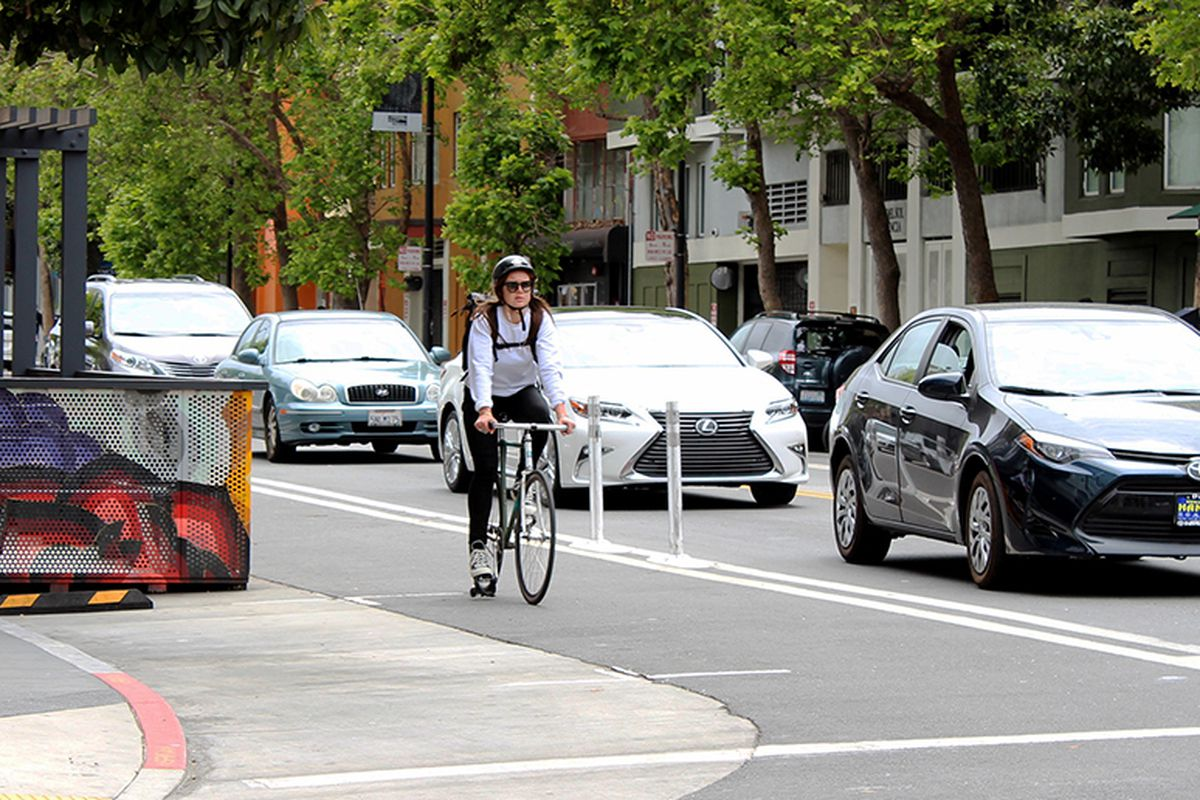 Woman cyclists with helmet riding along Valencia Street inside of a protected bike lane. Cars are at her left, safely separated by a barrier.