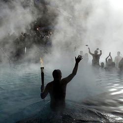 George DiCarlo waves to the crowd gathered at the end of his leg of the Olympic torch relay at Glenwood Springs hot springs pool on Feb. 2, 2002.