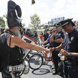 Police Capt. E.D. Patterson fist bumps with demonstrator Vermin Supreme during a protest march, Sunday, Sept. 2, 2012, in Charlotte, N.C. Demonstrators are protesting before the start of the Democratic National Convention.