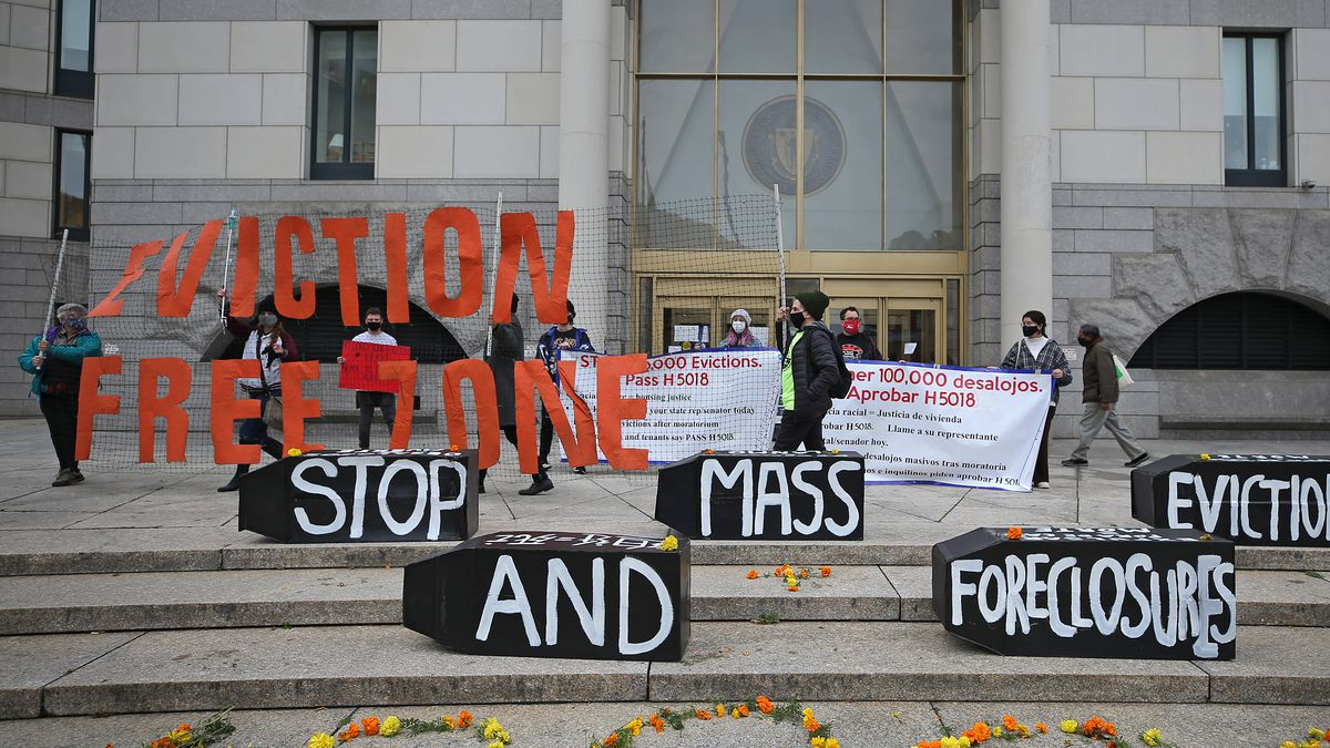 """Demonstrators with signs that read """"eviction free zone"""" and """"stop mass evictions and foreclosures."""""""