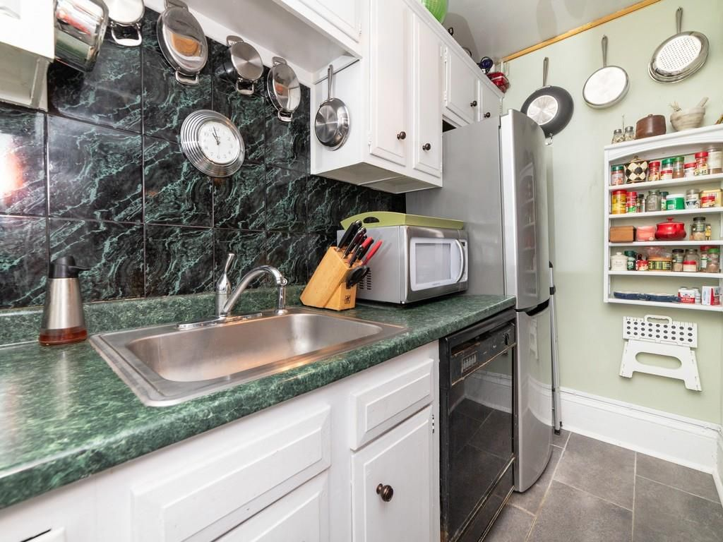 A small kitchen with a counter ending in a fridge.