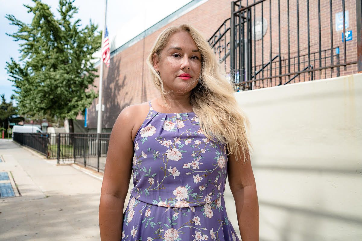 A woman with blonde hair and a purple floral patterned dress stands in front of a New York City School.