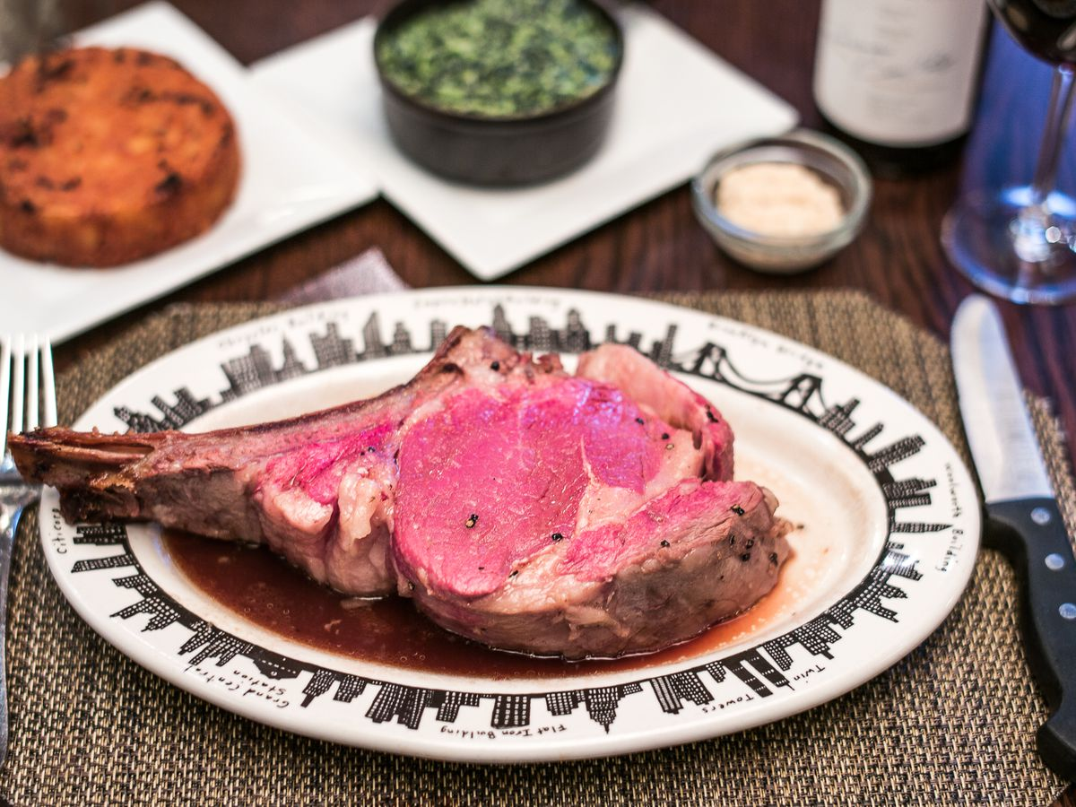 A piece of rare prime rib sits on an oval plate between a fork and a steak knife. In the background, there are small plates of sides and a wine glass.
