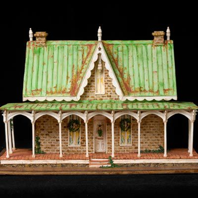 Amazing gingerbread house with a green roof with detail that makes it look rusted.