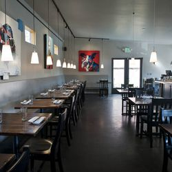 Revel's unfussy, simple, dining room relies on the striking, modern art on the walls. But, that's not all: the kitchen has been brought into the dining room and lends the room vibrancy and plenty of visual interest.