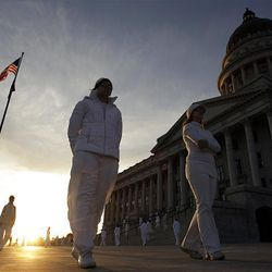 """Performers in Ernesto Pujol's durational art piece """"Awaiting"""" walk the grounds of the state Capitol in Salt Lake City Thursday. The performers, wearing all white, walked from various points in Salt Lake City to convene on the steps of the Capitol, where they walked up and down for 12 hours. Local artists and University of Utah students were involved in the performance."""