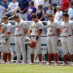 Texas Longhorns observe a moment of silence before their game against the Louisville Cardinals in the College World Series at TD Ameritrade Park Omaha on June 16, 2014
