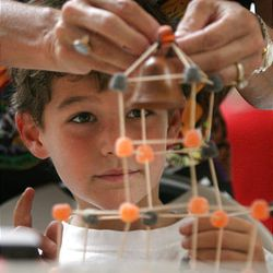 Dominic Blake, 6, of Salt Lake City, watches as his mother, Julie Blake, helps him tie a bell onto the tower of his Capitol replica made out of toothpicks and gumdrops at the fifth annual event.