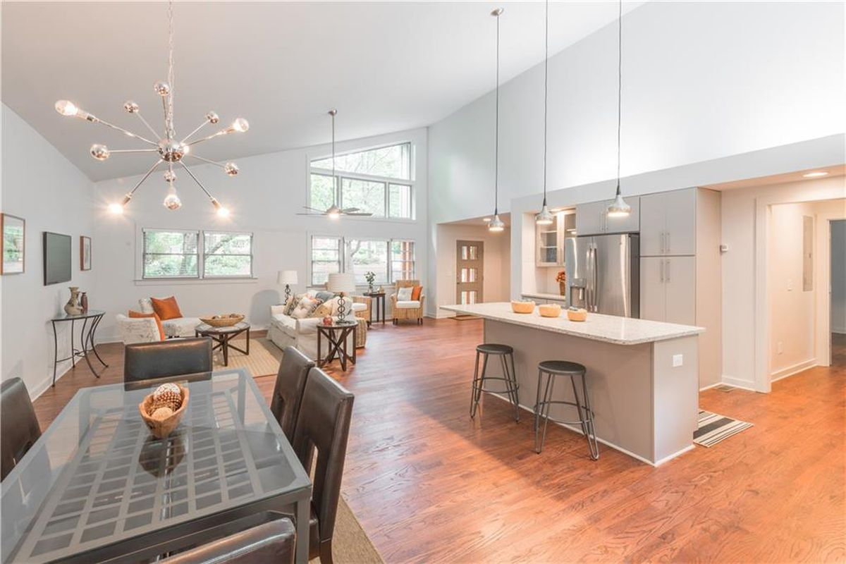 An open kitchen and living room with vaulted ceiling.
