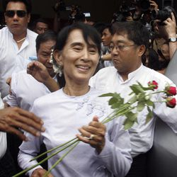Myanmar pro-democracy leader Aung San Suu Kyi receives flowers from supporters as she leaves the headquarters of her National League for Democracy party in Yangon, Myanmar Monday, April 2, 2012. Suu Kyi claimed victory Monday in Myanmar's historic by-election, saying she hoped it will mark the beginning of a new era for the long-repressed country.