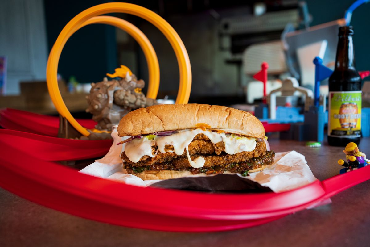 A large sandwich with dripping cheese sits next to toys.