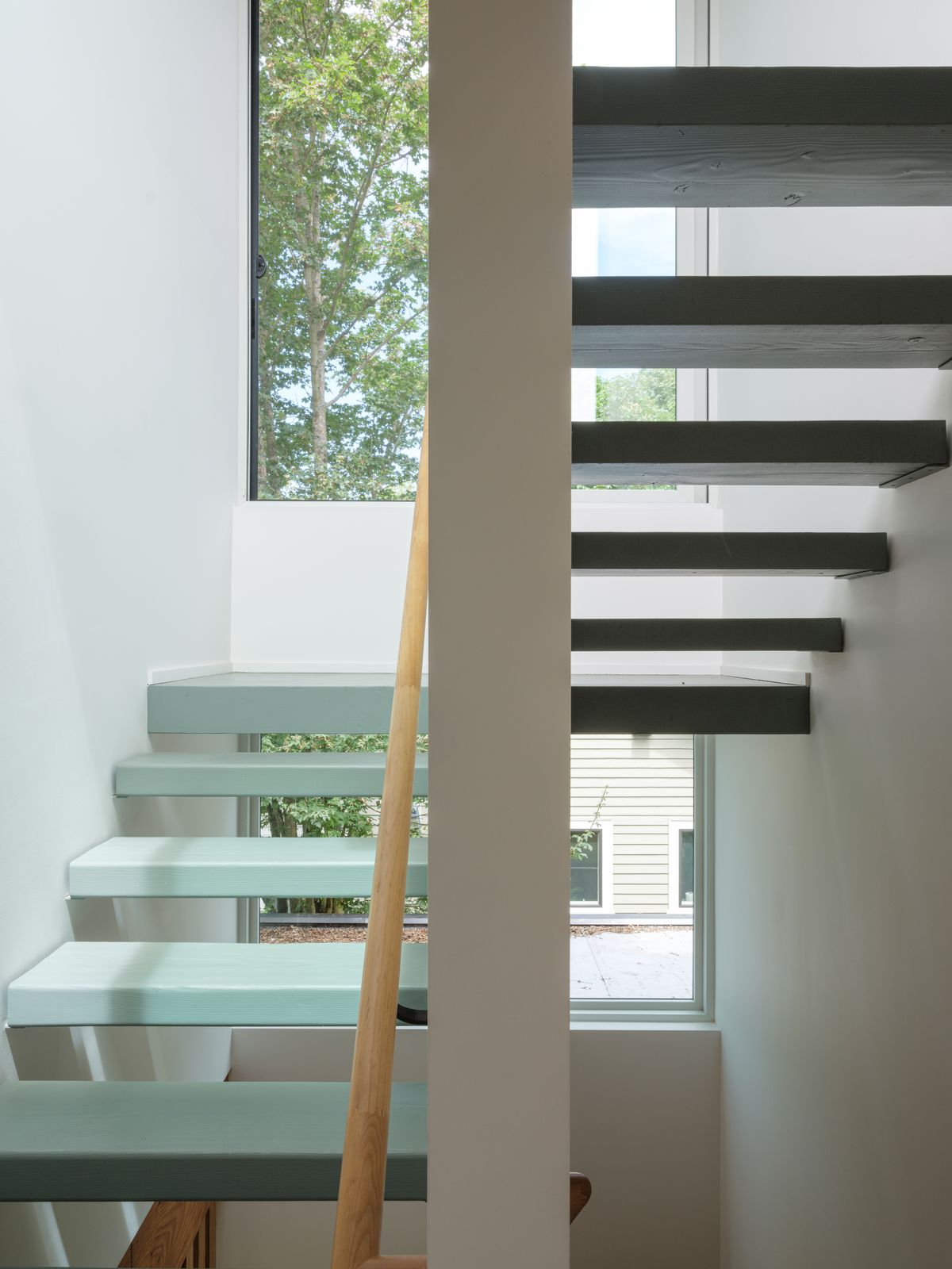 A white stairwell with a set of tall windows. The stairs are light blue. There is a wooden bannister.