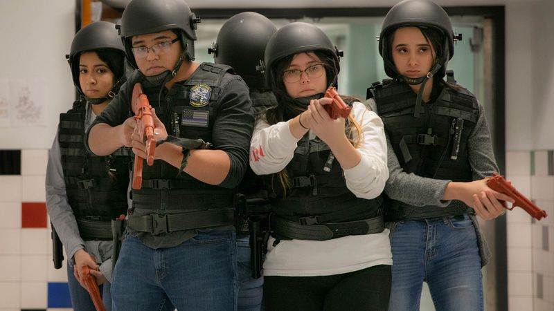 A group of high school students in riot police garb clusters in a hallway, holding fake plastic guns.