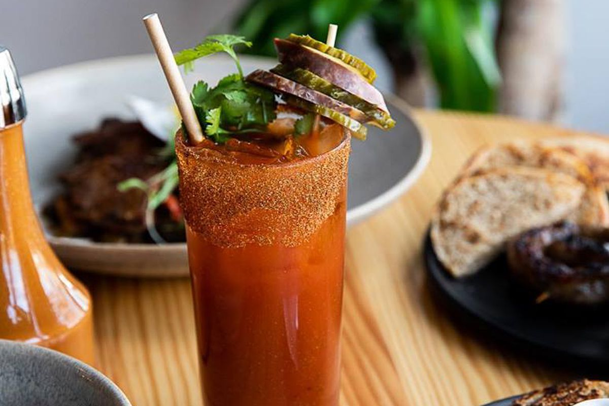 A bloody mary with slices of sausage skewered on the rim from Marrow.