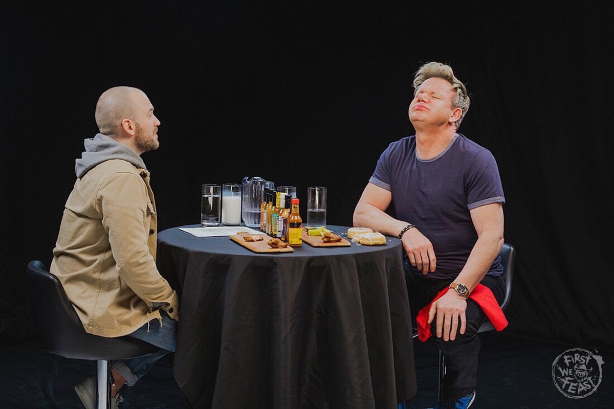 Two men sit at a table; one challenges the other to eat spicy-hot chicken wings.