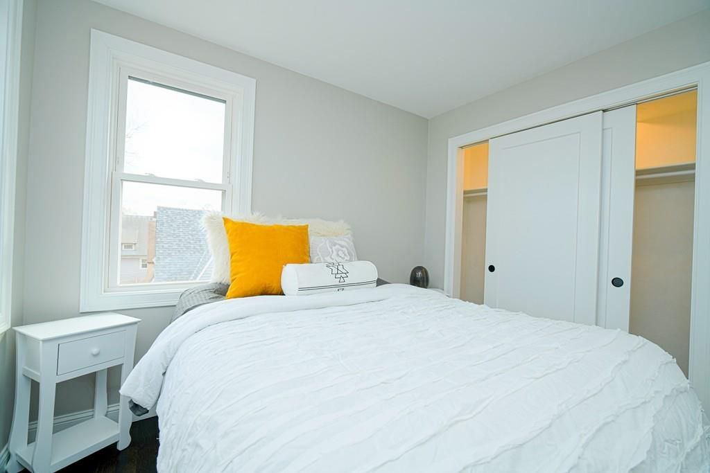 A bedroom with a bed next to a closet.