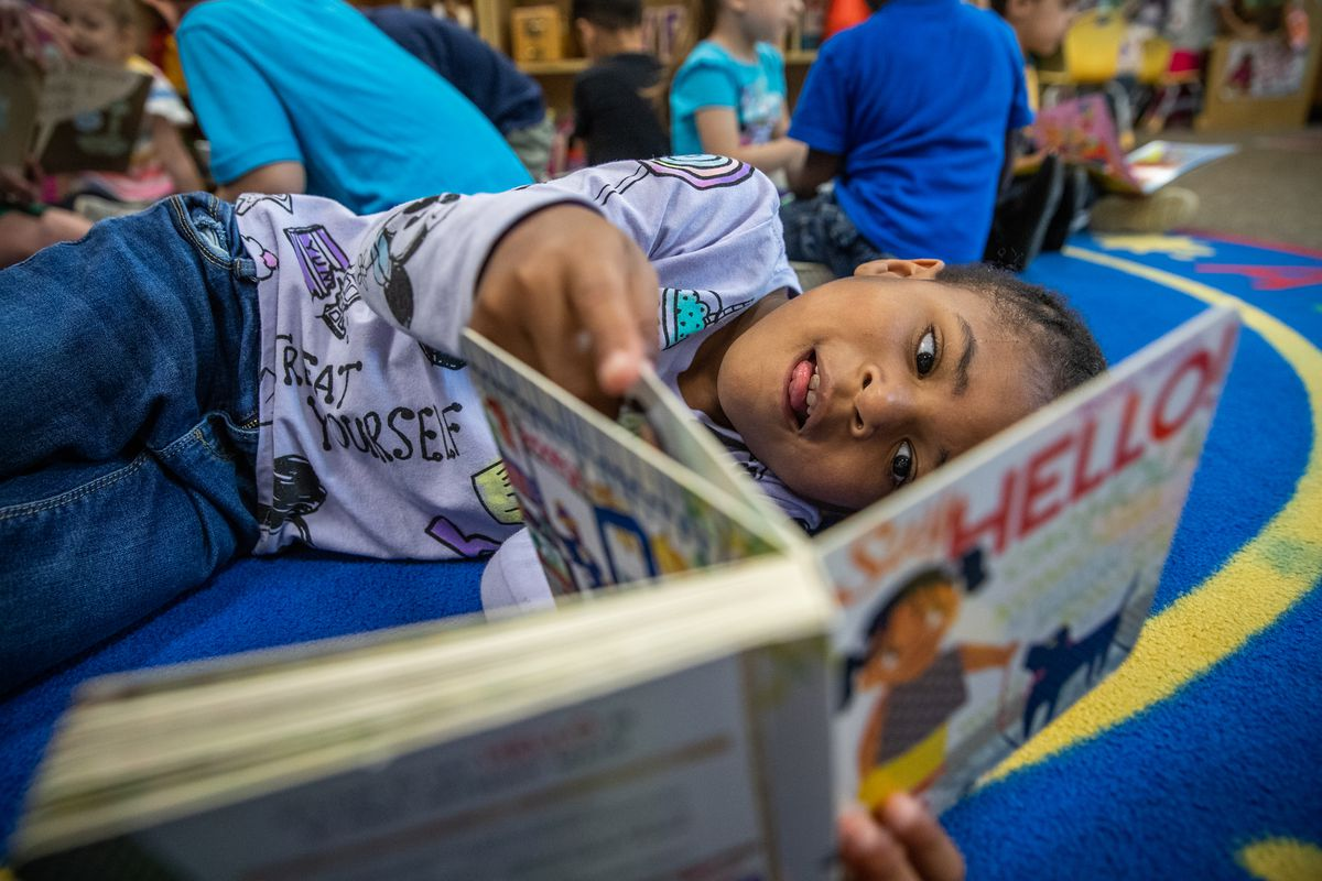 Five-year-old reads a book alongside lying on a rug alongside her classmates.