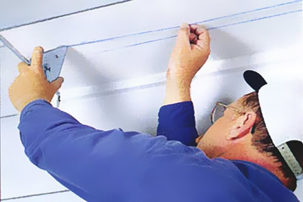 Person marking ceiling to prepare for soffit vent installation.